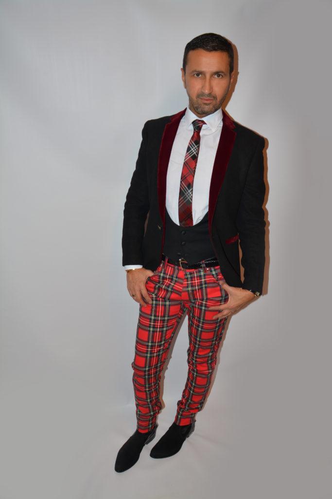 Tenue pour homme stylé plutôt originale, veste et gilet noirs de smoking et un pantalon à tartans rouges. Un style original et décalé.