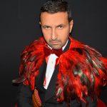 L'homme ange en smoking noir avec une cape en plumes rouges