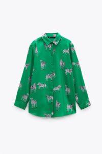 Chemise vert/écru avec col à revers et manches longues. Fermeture par boutons sur le devant