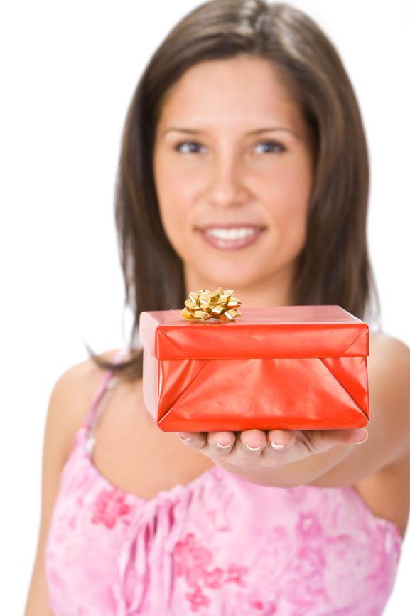 Une femme, la quarantaine au sourire très agréable offrant un cadeau à autrui.