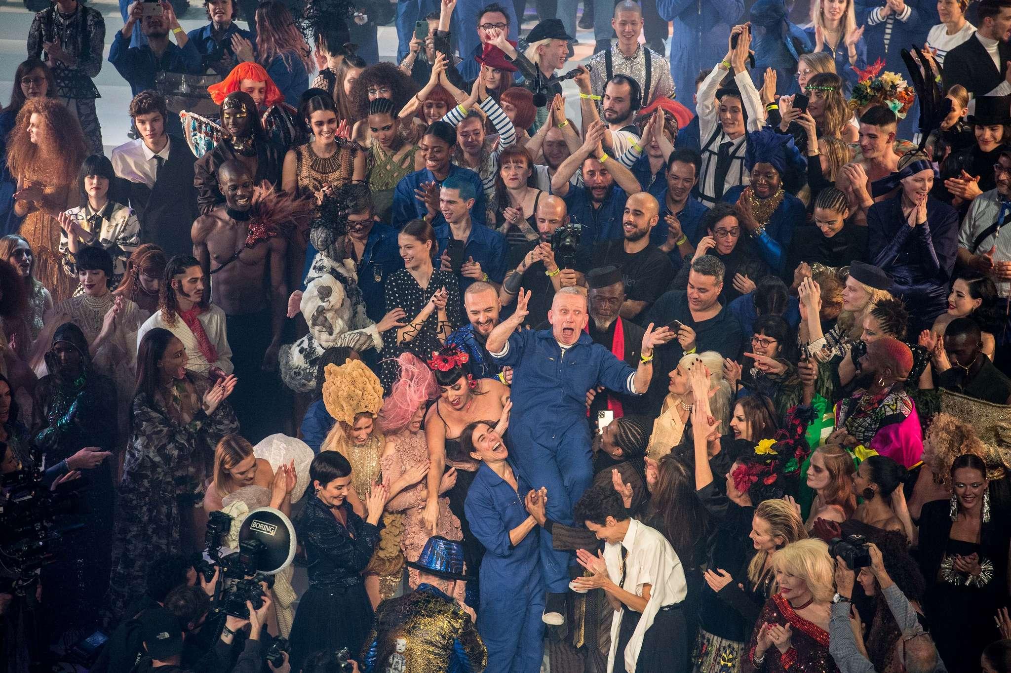 On voit Jean-Paul Gaultier en combinaison bleue heureux et joeux entouré de tous ses amis proches, entrain de fêter le dernier défilé haute couture du créateur Jean-Paul Gaultier en leur compagnie.