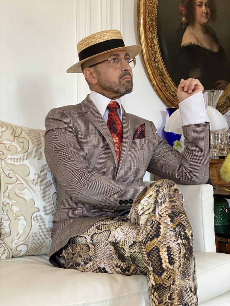 Tenue pour homme plutôt originale avec chapeau cravate et pochette. Des lunettes de vue binocles et un pantalon motif animalier. Un style proche du dandy.