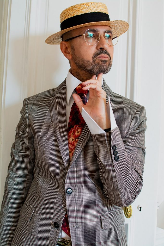 Tenue homme originale avec chapeau cravate et pochette. Des lunettes de vue binocles et un pantalon motif animalier. Un style proche du dandy.