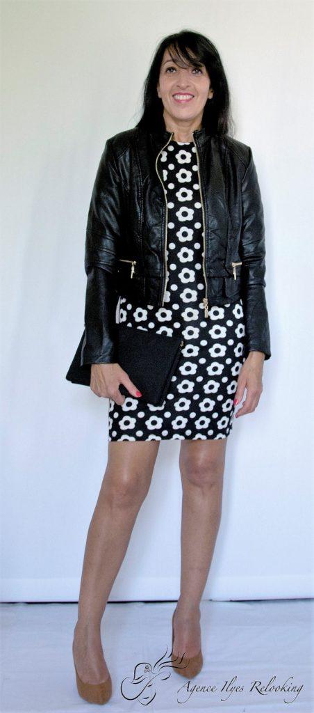 Il s'agit d'une tenue total monochrome pour femme, composée d'une petite robe noir et blanc, d, d'un petit blouson noir et d'une paire d'escarpins noirs.