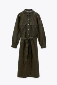 Robe kaki avec col à revers, manches longues et poignets plissés. Poches plaquées à rabat sur la poitrine. Ceinture à nouer de même tissu. Fermeture par boutons en métal sur le devant