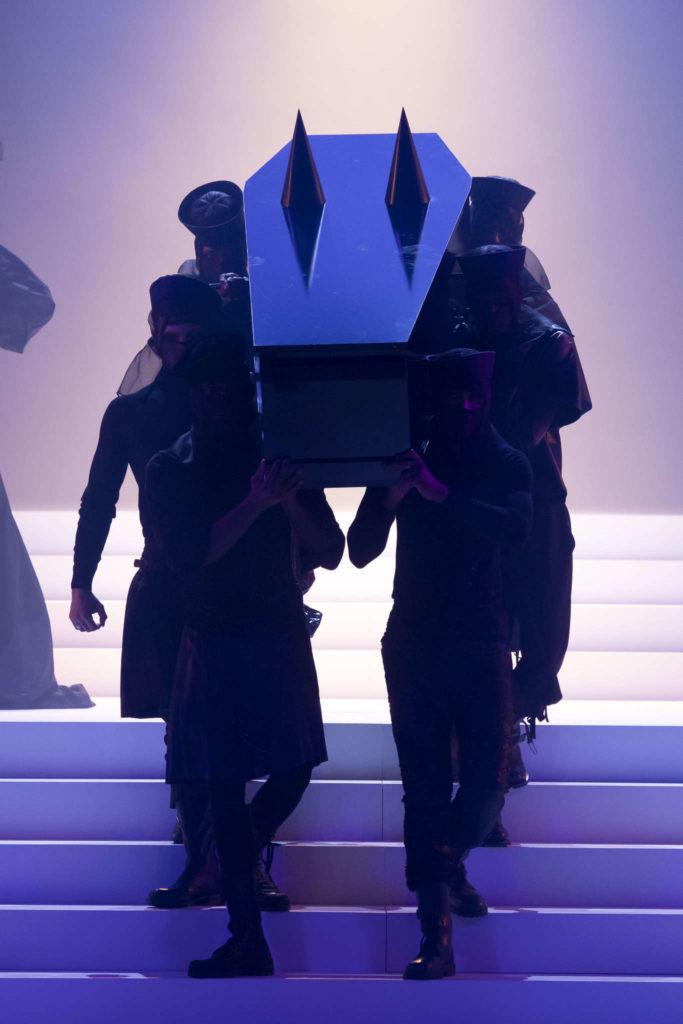 Six danseurs en kilt, marcel et rangers tels des porteurs soutenant un cercueil noir orné de mamelons coniques géants – rappelant les légendaires soutiens-gorge et corsets coniques que Jean-Paul avait imaginés pour Madonna dans le cadre de sa tournée « Blonde Ambition » en 1990.