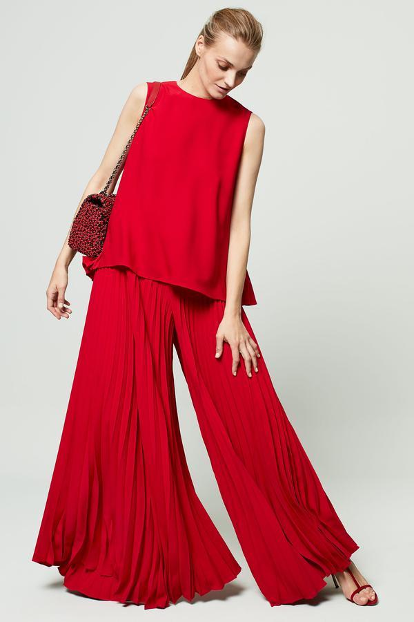 Top et pantalon en crêpe plissée d'un beau rouge accéssoirisée par un joli petit sac porté épaule de chez Carolina Herrera