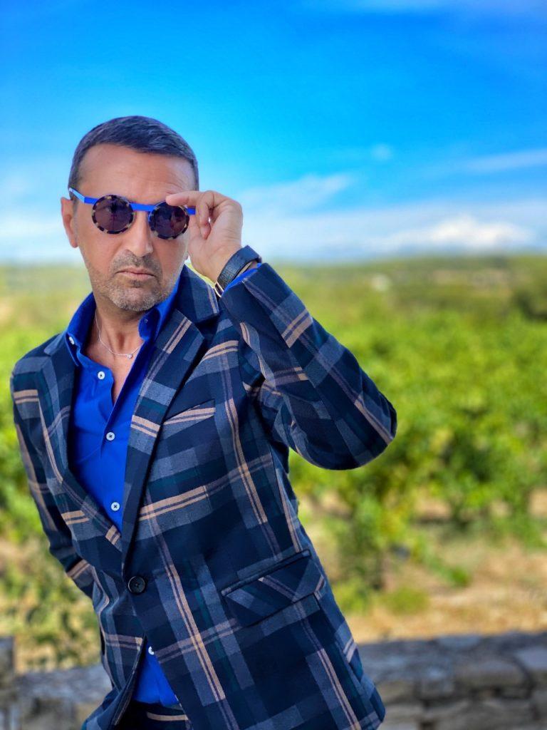 Le model porte un très beau costume à carreaux bleus, d'une coupe contemporaine et slim fit assorti d'une chemise bleu roi et une paire de chaussures mocassins bleues. L'accessoire principal est une paire de lunettes de soleil bleue pour assure un très beau monochrome bleu.