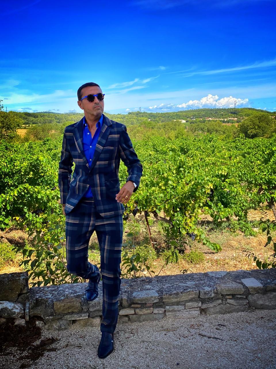 Ce model porte un très beau costume à carreaux bleus, d'une coupe contemporaine et slim fit assorti d'une chemise bleu roi et une paire de chaussures mocassins bleues. L'accessoire principal est une paire de lunettes de soleil bleue pour assure un très beau monochrome bleu.